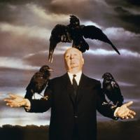 Alfred Hitchcock posing with crows on his arms